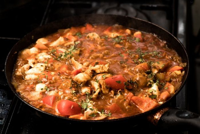 Steam rising from boiling pot of chicken and tomato souce.